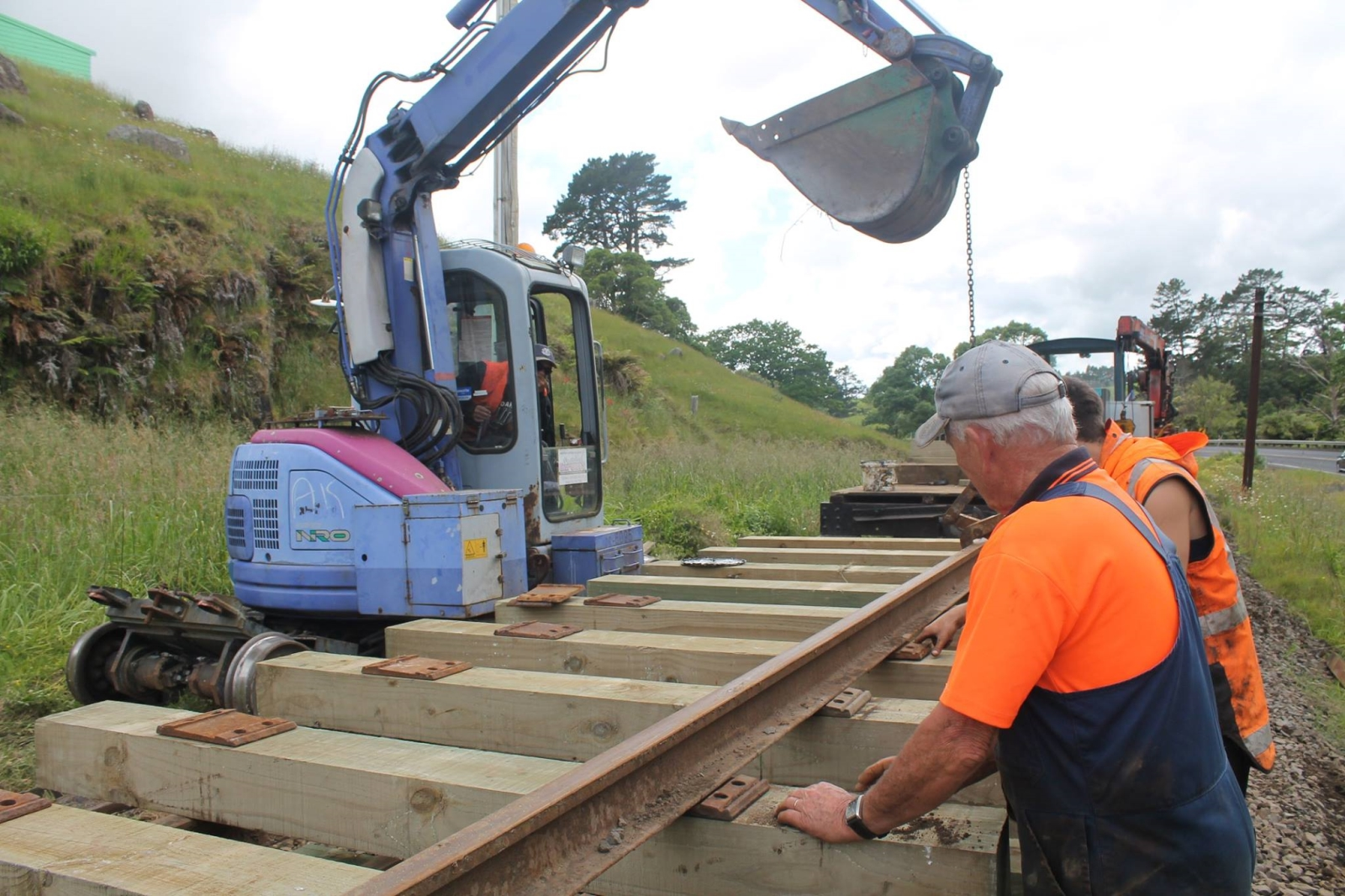 Ops Manager assisting digger driver guide rail on top of railway fishplates.
